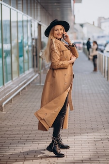 Молодая женщина в черной шляпе с помощью телефона