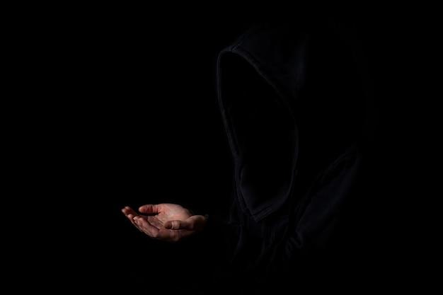 검은 후드 얼굴을 한 젊은 여성은 어두운 검은색 배경에 손바닥을 뻗은 상태로 보이지 않습니다.