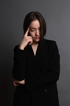 暗い灰色の背景に黒のジャケットの若い女性。感情を持つ少女。悲しい女の子