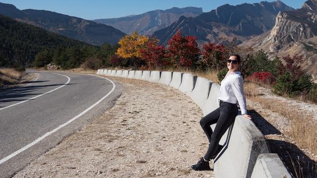 黒のジーンズと白いパーカーの若い女性は、色付きの秋の木々と青い空の下の丘陵の風景に対して山の道路の障壁の近くに立っています
