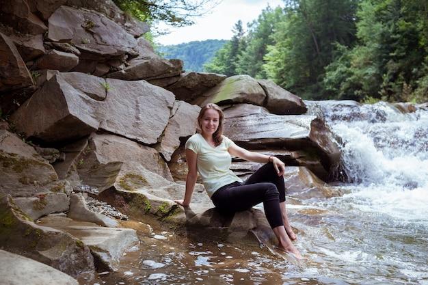 黒のレギンスを着た若い女性が水しぶきの滝の近くの石に座っています。平和な白人旅行者は美しい小川に座っています。