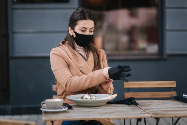 검은 보호 마스크에 젊은 여자는 점심을 먹기 위해 검은 장갑에 넣어.
