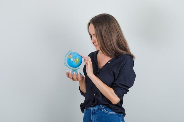 Молодая женщина в черной рубашке, джинсовых шортах, выбирая место назначения на земном шаре пальцем