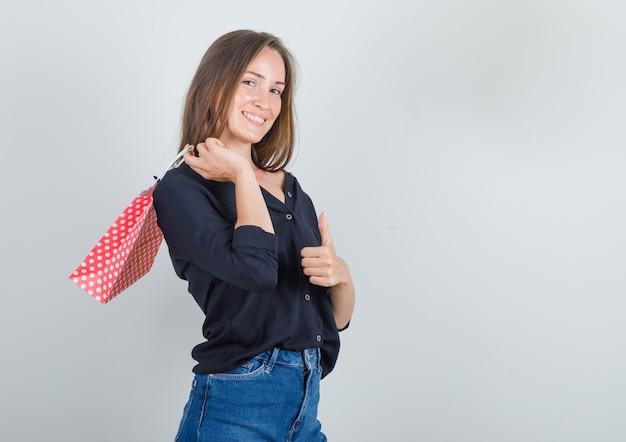 黒のシャツを着た若い女性、親指を上にして紙袋を持って陽気に見えるジーンズのショートパンツ