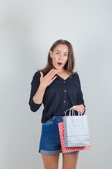 黒のシャツを着た若い女性、紙袋を持って驚いたジーンズのショートパンツ