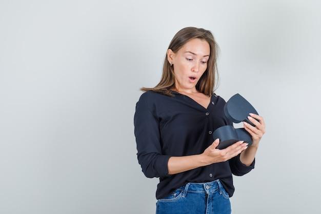 黒のシャツを着た若い女性、ギフトボックスを見て驚いたジーンズのショートパンツ