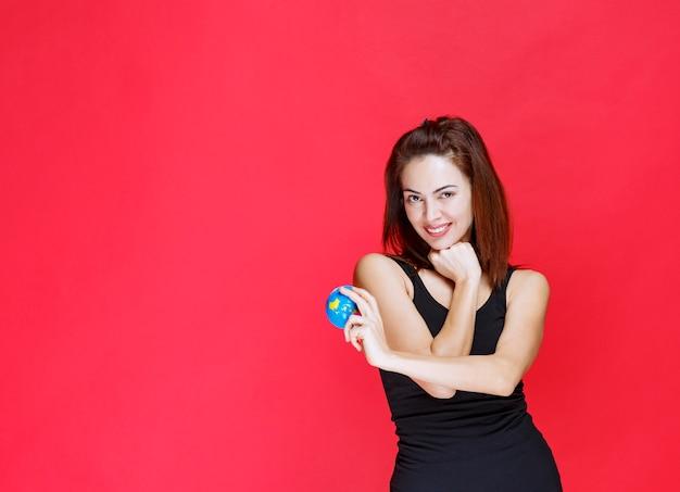 Молодая женщина в черной майке, держащей мини-глобус мира