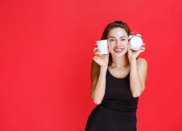 Молодая женщина в черной майке держит будильник и чашку напитка