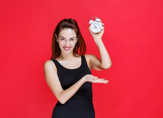 目覚まし時計を保持している黒い一重項の若い女性