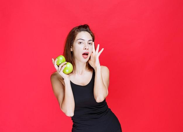 青リンゴを保持し、驚いて見える黒い一重項の若い女性