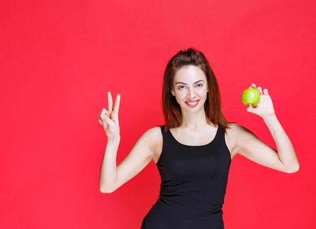 青リンゴを保持し、平和の兆候を示す黒い一重項の若い女性