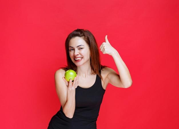 緑のリンゴを保持し、親指を表示して黒い一重項の若い女性