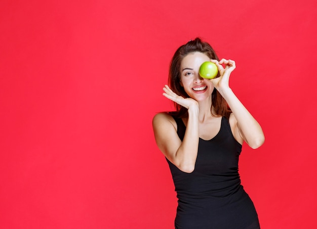 彼女の目に青リンゴを保持している黒い一重項の若い女性