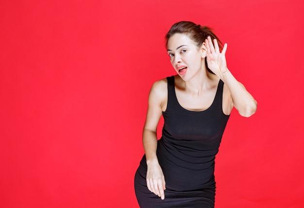빨간 벽에 서서 주의 깊게 듣고 있는 검은색 싱글렛을 입은 젊은 여성