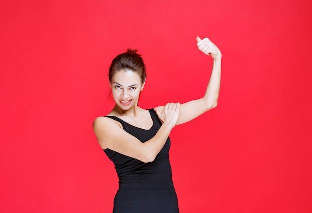 赤い壁に立って親指を立てて黒い一重項の若い女性