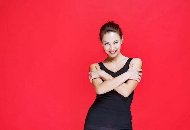 붉은 벽에 서 있는 검은색 중항에 젊은 여자