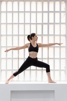 彼女のスタジオの大きな窓の横でヨガのポーズをしている黒いスポーツウェアの若い女性。テキスト用のスペース。 Premium写真