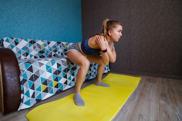 Молодая женщина в черной спортивной одежде занимается йогой, стоя в позе переднего изгиба, выполняет упражнение, спортивная девушка занимается дома или в студии йоги с серыми стенами, растягивает тело