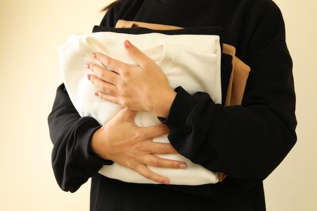 Молодая женщина в черной толстовке держит три толстовки
