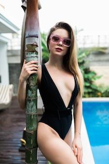 ヴィラで黒い水着を着た若い女性、ヤシの木の景色。若い白人女性の体型にフィットします。