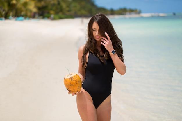 ビーチでココナッツカクテルと黒の水着で若い女性