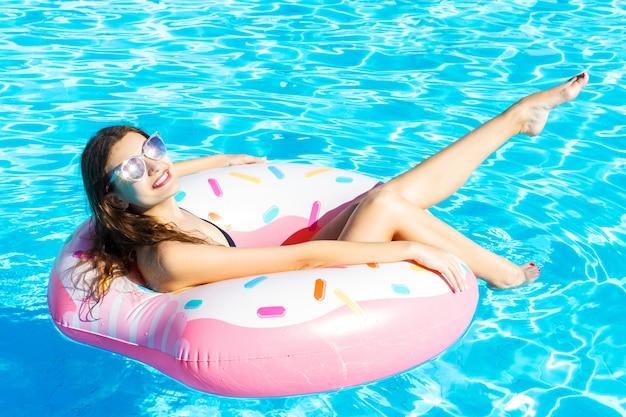 검은 수영복에 젊은 여자는 도넛 링에서 휴식입니다