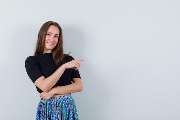 검지 손가락으로 오른쪽을 가리키고 매력적으로 보이는 검은 색 t- 셔츠와 파란색 치마에 젊은 여자