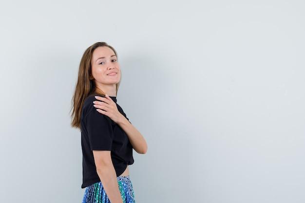 검은 색 t- 셔츠와 파란색 치마에 똑바로 서서 어깨 너머로보고 행복을 찾는 젊은 여자