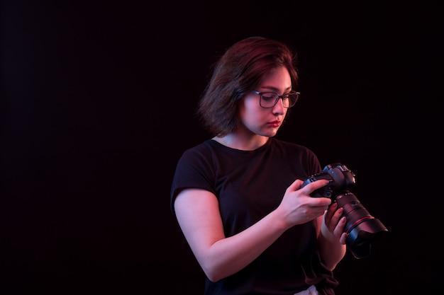 Молодая женщина в черной футболке с камерой