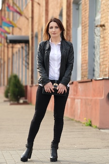 黒のタイトなデニム、白いシャツ、通りの革のジャケットの若い女性