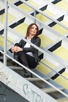 金属の階段に座っている黒のタイトなデニム、白いシャツ、革のジャケットの若い女性