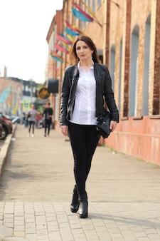 黒のタイトなデニム、白いシャツ、革のジャケットの若い女性が通りを歩く