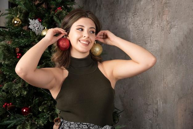 クリスマスの装飾が施された部屋で光沢のあるボールのイヤリングを作る黒いトップの若い女性