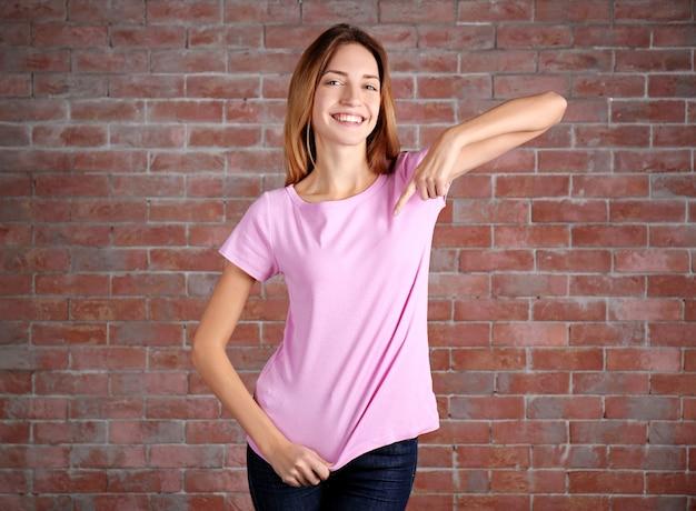 レンガの壁に立っている空白の色のtシャツの若い女性
