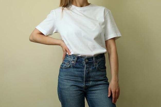 Молодая женщина в пустой футболке на бежевом фоне