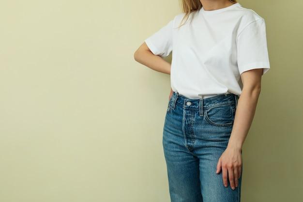 ベージュの表面に対して空白のtシャツの若い女性