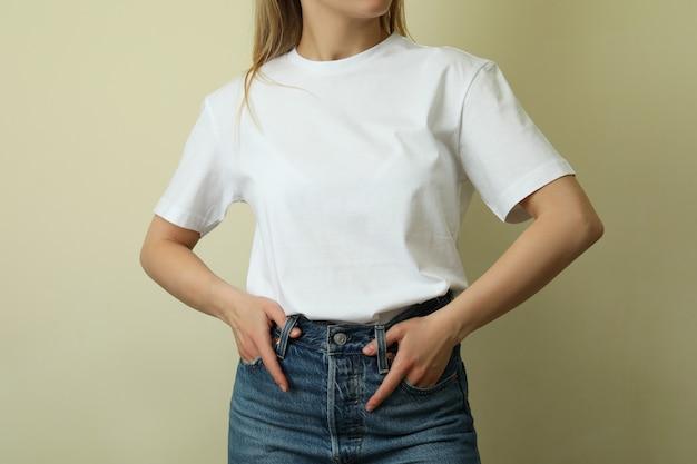 Молодая женщина в пустой футболке против бежевого