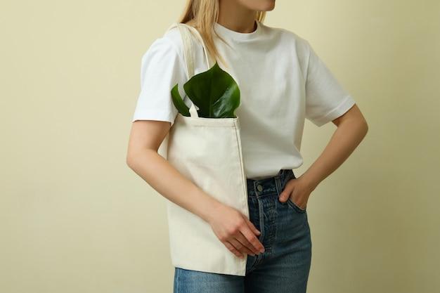 ベージュの表面に対してバッグと空白のtシャツの若い女性