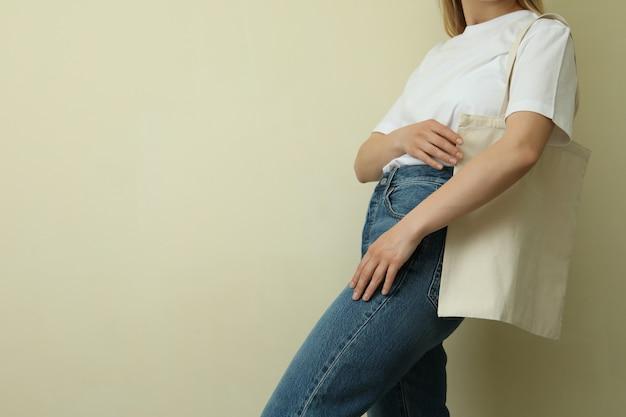 Молодая женщина в пустой футболке с сумкой против бежевого
