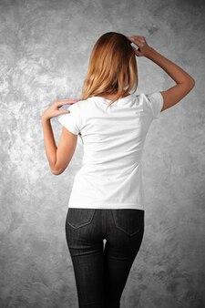 灰色のテクスチャ壁に立っている空白の白いtシャツの若い女性