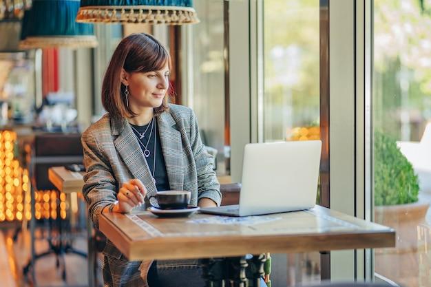Молодая женщина в пиджаке с ноутбуком в кафе у окна. профессии - блогер, фрилансер и писатель. фрилансер, работающий в кафе. обучение онлайн.