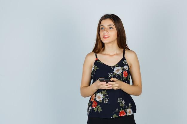 스마트폰을 들고 있는 블라우스를 입은 젊은 여성은 멀리 바라보고 잠겨 있는 전면 전망을 바라보고 있습니다.
