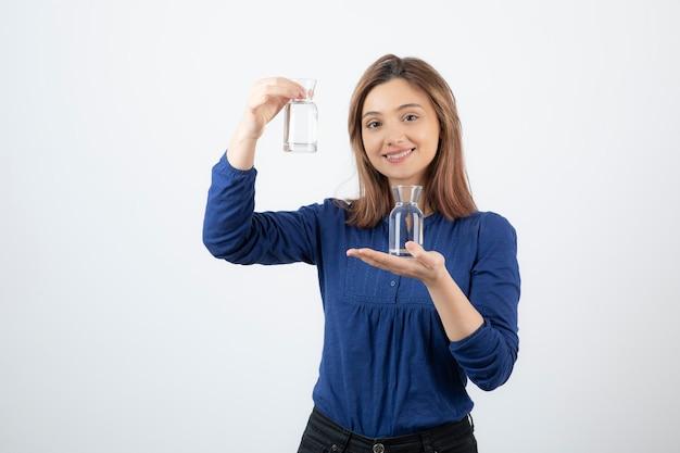 彼女の手に水を保持している青いブラウスの若い女性。