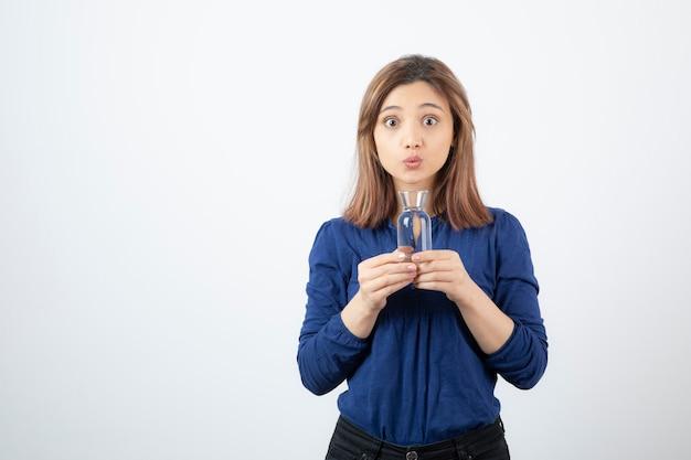 水を保持している青いブラウスの若い女性