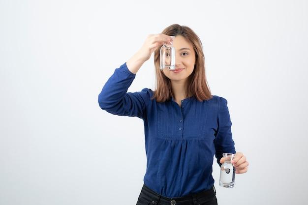 Молодая женщина в голубой блузке, показывая стакан воды.