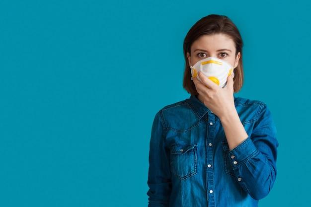 파란색 옷을 입은 젊은 여자는 여유 공간이있는 파란색 벽에 뭔가를 광고하는 얼굴에 의료 마스크와 함께 포즈를 취하고 있습니다.