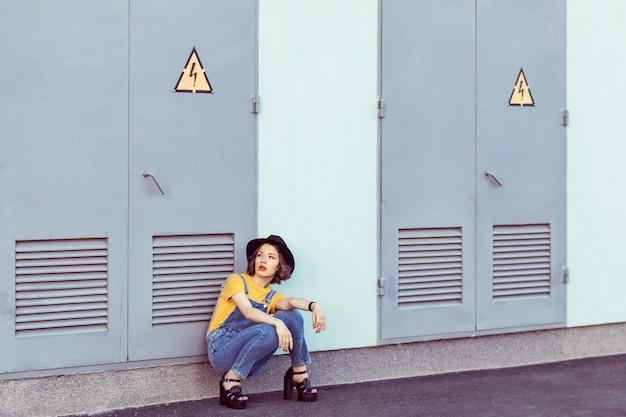 青いデニムのオーバーオールと黄色のtシャツを着た若い女性が、工業ビルの近くでポーズをとっている間、官能的な黒い帽子をかぶっています。夏の野外撮影