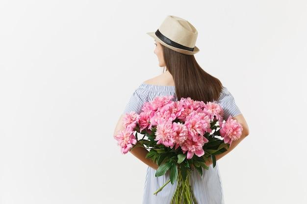 파란 드레스를 입은 젊은 여성, 모자는 흰색 배경에 격리된 등 뒤에 아름다운 분홍색 모란 꽃다발을 들고 있습니다. 성 발렌타인 데이, 국제 여성의 날 개념. 광고 영역입니다.