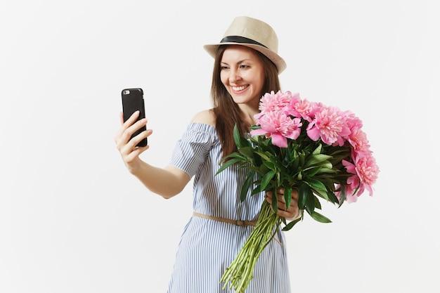파란 드레스를 입은 젊은 여성, 아름다운 분홍색 모란 꽃다발을 들고 모자를 쓰고 흰색 배경에 격리된 휴대전화로 셀카를 찍고 있습니다. 성 발렌타인, 국제 여성의 날 휴일 개념.