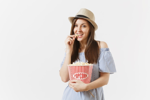 파란 드레스를 입은 젊은 여성, 흰색 배경에 격리된 양동이에서 팝콘을 먹고 있는 영화 영화를 보고 있는 모자. 사람들, 영화의 진지한 감정, 라이프 스타일 개념. 광고 영역입니다. 공간을 복사합니다.